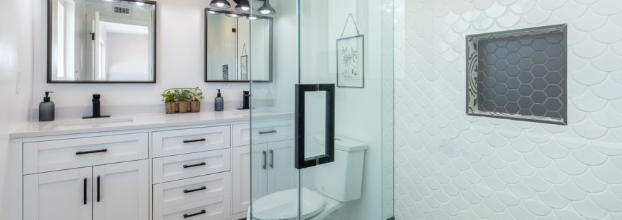 Photo of a bathroom with ornate cabinets, a walk-in shower and a toilet. There is a very pretty black and white tiled floor.